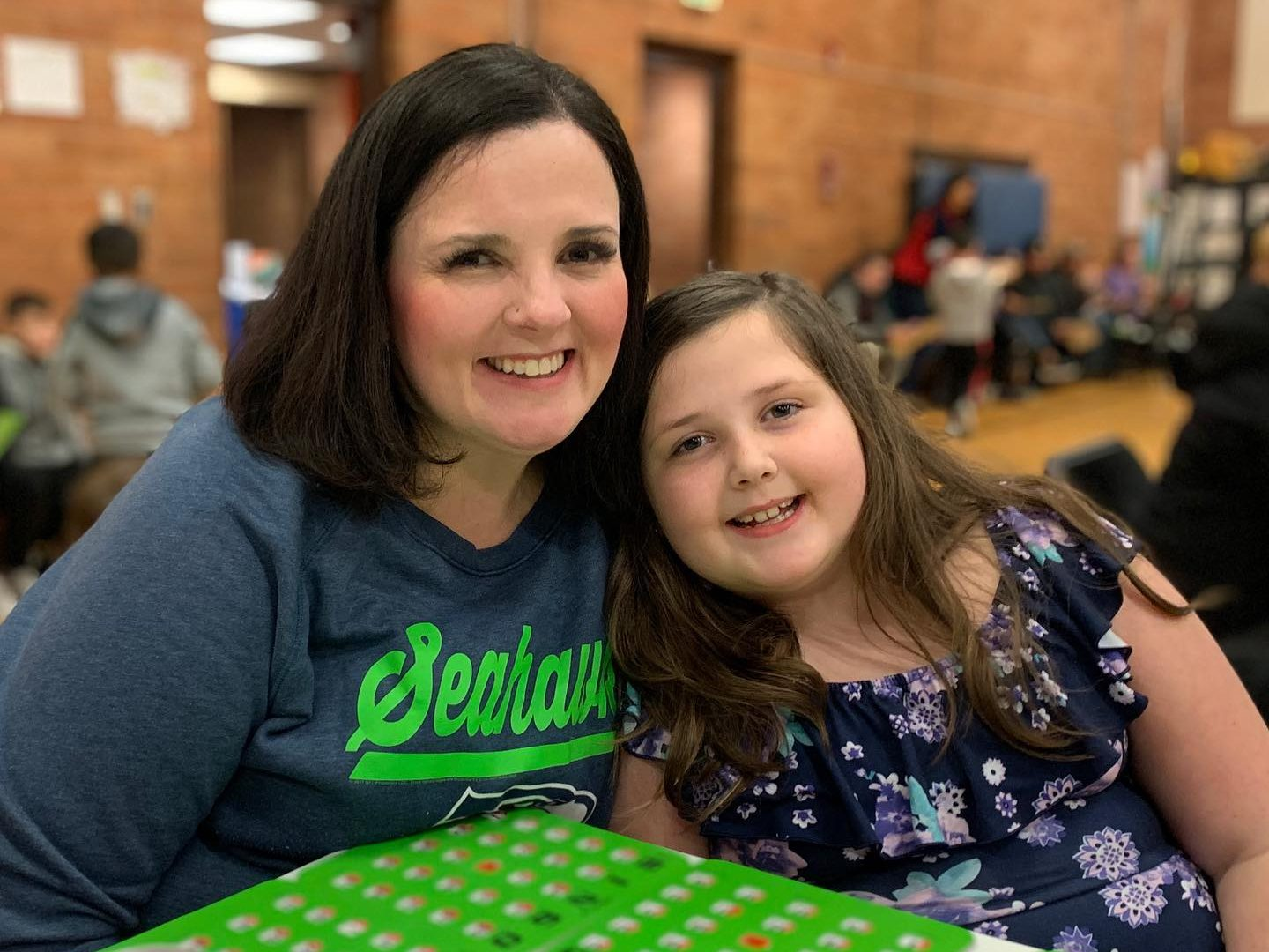 Mother and daughter at elementary school bingo night smiling